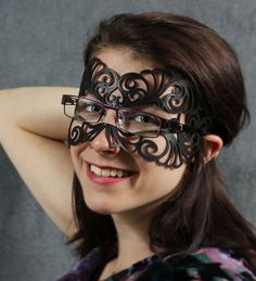 Leather filigree half-mask in black, designed for glasses-wearers. Looks like the nose bridge is left cut-out, and then glasses arms can go over the mask and/or through the holes in the filigree. Total weight 0.5 oz/12g, comes in several colors, with an elastic band.