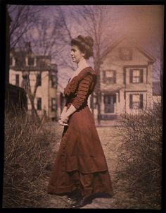 Woman wearing red dress with houses in background, circa 1915. Autochrome, not hand-tinted. George Eastman House Collection on Flickr