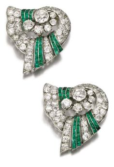 Emerald and diamond double clip brooch, 1930s. Each of scroll design, set with circular-cut diamonds and lines of calibre emeralds, accompanied by brooch fitting allowing both clips to be worn together.