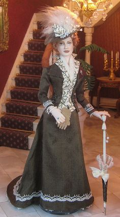 Elisa Doll, it is 1893 and a lovely lady is ready to go out for a walk into the beautiful colors of Autumn. She wears a tailor made dark green silk with lace walking costume over a silk vest. Tiny buttons close this vest.