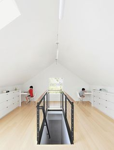 Bamboo flooring and custom built-ins—fashioned from medium-density fiberboard with a white-lacquer finish—brightened the 650-square-foot attic. The custom-designed blackened-steel balustrade has cable inserts and a walnut handrail.