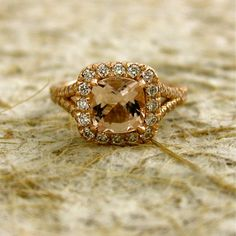 Halo style, rose gold, split shank engagement ring with cushion cut, pink sapphire.