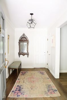 Hallway with wooden floors, white walls, patterned rug, antique mirror, light grey bench, and glass light fixture