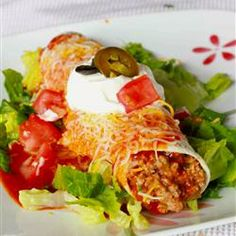 Fabulous Wet Burritos.     Flour tortillas are filled with a mixture of ground beef, refried beans, and chiles then topped with a generous amount of sauce and cheese.