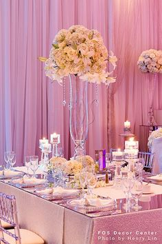 White wedding floral centerpieces in glass vases with hanging crystals