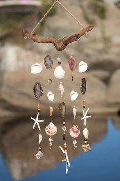 Earth tone colors of driftwood, agate and shells make this wind chime a one of a kind beauty. It showcases five geo agate slabs and two agate druzy rocks. Agates are considered a semi-precious gemstone. A stone of strength, the agates most noticeable properties over all are balancing yin/yang energy, courage, healing and calming. Several different types of shells make up this beautiful mobile including purple pecten, cockle shells, starfish, misc cut shells , brown chula shells and beads.