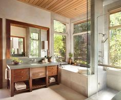 Custom vanity in the bathroom clad from walnut adds warmth to the setting