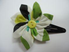 Jolie barrette en coton dans les tons noir, vert, jaune et blanc, en forme de fleur, avec un coeur en bouton jaune. La barrette est une pince clic-clac noire de 5 cm.  Tarifs : 4€ + fdp