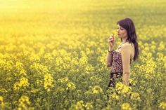 Attractive genuine young woman enjoying the warm summer sun in a wide green and yellow meadow sniffing a blossom. Summer Sun, Yellow Flowers, Falling In Love, Things To Think About, Green, Commercial, Magazine, Warehouse, Newspaper