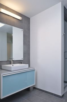 Perhaps you aren't keen to adorn your bathroom walls with bright blue tile. Take inspiration from this striking minimalist bathroom; go with a neutral gray wall and floor tile, and inject color via a sky-blue vanity. This is a good palette for a bathroom that doesn't receive much natural light. The white walls help brighten the room.