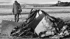 Un oficial del ejército argentino camina al lado de un avión de guerra británico derribado