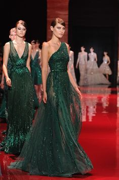 """[I wonder if they follow a schedule for which body part to leave exposed?  You know, visible boobs on Mondays, visible hips and legs on Tuesdays, """"I see her crack, so it must be Wednesday"""" and so on.  But I must admit I like the sparkly green fabric.] Dois vestidos verde-escuro maravilhosos, confesso que sou mais fã do de um ombro…"""