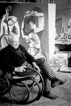 Pablo Picasso sitting in a rocking chair in his studio, with one of his large finished canvases behind him.