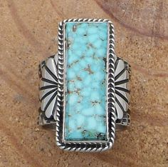The intricately stamped and oxidized ring has a rectangular turquoise stone in a smooth silver bezel with recessed silver rope trim and raised stamped fan accents.  The turquoise stone is from the Turquoise Mountain mine and is bright blue/green with blue and brown marbled matrix.  Sunshine Reeves, Navajo