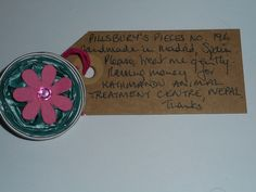 Pillsbury's Pieces No, 196. Pin with metallic green capsule with bright pink flower. In exchange for a donation to KATHMANDU ANIMAL TREATMENT CENTRE, Nepal. Available at St. George's Church, Madrid on Saturday 13 June from 11.00 - 15.00.