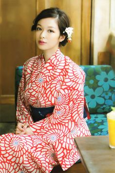 Young woman in a red and white modern kimono, with a flower in her hair