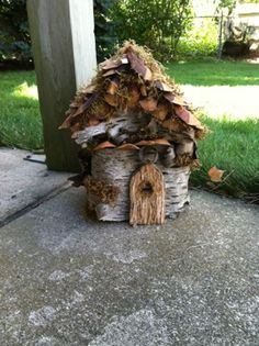 Fairy Garden House - bought Michael's 2 story birdhouse (five dollars), wrapped, hotglued and stapled birch bark around it.  Glued oversize pine cone pieces to the roof as shingles.  glued spanish moss in holes, fashioned door from dollar birdhouse from Michaels, glued maple leaf stems as window pane, teabag back as curtain/window shade.  Approx. height: 9.2 inches.  Plan to add tiny glitter in fall, 2012.