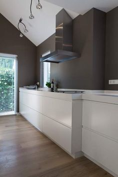 Moderne strakke, lichte keuken tegen donkere wand