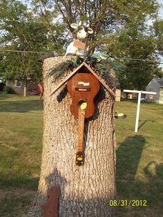 Decorated tree trunk, guitar bird house,  welcome cow and birds, cat looking down at the bird and frog at the top.