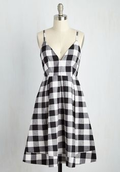 Enjoying oysters al fresco in this cute checkered dress, you can't help but remark on what a picnic perfect ensemble it is! Topped with slim straps, a plunging V-neckline, and a pleated skirt, this black-and-white, cotton frock will bring a smile to your face wherever it's worn!