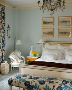 Beautiful bedroom by Timothy Whealon. Serene combination of lightest turquoise and cream is enlivened by a big lovely blue and cream floral on both a bench and drapes. Nailhead bed and subtle geometric rug give touch of edge to this soft space. Love the dangling chandelier, the sconces, the grouped prints above the bed, garden stool, and a Hermes throw draped over at Louis XVI armchair.