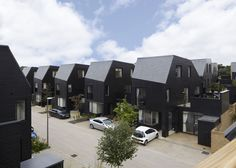 Suburban housing development in Essex by Alison Brooks Architects that reinterprets the local rural architecture of wood and sloping roofs.