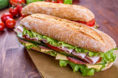 Two Long Ciabatta Sandwiches with lettuce, slices of fresh tomatoes, cucumber, ham, salami and cheese - stock photo Sandwich Sous-marin, Baguette Sandwich, Submarine Sandwich, Healthy Sandwiches, Wrap Sandwiches, Pan Baguette Receta, Tasty, Yummy Food, Meat And Cheese
