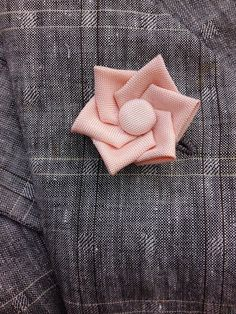 A pink lapel pin flower boutonniere for elegant men and women, made in the Japanese tsumami kanzashi style! This attention-grabbing pin is a unique fashion accessory no one else can own. I used a pink silk sailcloth to make the flower, added a cover button to the center, and mounted