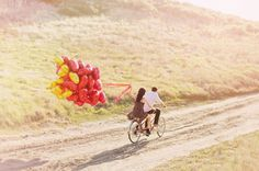 riding away on a tandem bike with heart balloons