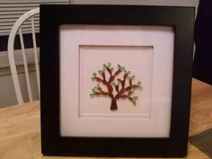 """Framed and double matted """"Tree of Life"""" with brown and green beach glass."""