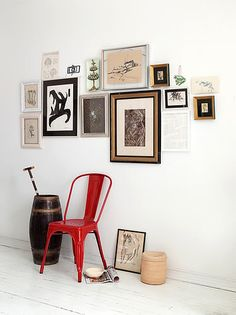 great gallery wall with a warm pop ffom a red chair