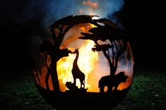 A beautiful sculptural firepit with an African Safari scene hand carved around the ball. A pair of elephants make their way around the ball, blissfully unaware of the lion that awaits them. African Safari, Outdoor Rooms, Cool Photos, Interesting Photos, Pumpkin Carving, Hand Carved, Elephant, Scene, Sculpture