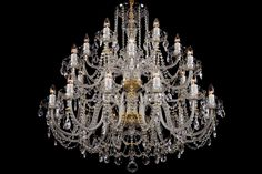 A colourless crystal chandelier with twenty-four light bulbs and golden metal parts.