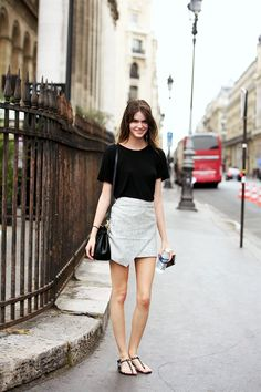 Model Vanessa Moody looks the epitome of casual chic in Paris wearing a classic black tee, neutral asymmetrical wrap skirt and embellished flat sandals.