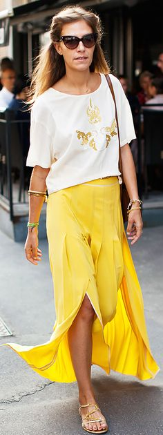 Loosely fit shirt with gold embellishment, yellow maxi skirt with slit openings, and gold sandals