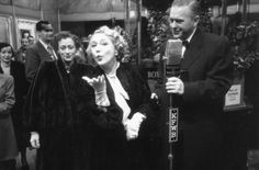 Mary Pickford blows a kiss as she is interviewed at the film premiere of Death of a Salesman | 1951
