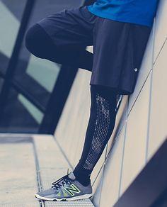 Il porte un t-shirt bleu, des shorts noirs, des pantalons de jogging noirs et gris, et des baskets gris and jaunes.
