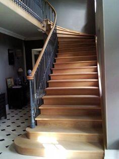 Très bel escalier en bois de style ancien avec marches débordantes en chêne. Rambarde en fer forgé peint en gris bleu. Escalier classique d'époque qui s'intègre dans un intérieur ancien, classe et chic.