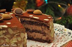 """Dragii mei, am facut acest Tort Toffifee cu gandul la voi. Si cu gandul la Bogdi, care adora aceste bombonele de caramel, umplute cu nuga si ciocolata. Pentru ca noul an sa ne gaseasca mai veseli, mai ancorati intr-un decor dulce si optimist :P Nu va spun prea multe, ca altadata, ci doar un simplu si din inima: """"La multi ani!!!!!!"""" Si mari, mari multumiri pentru ca mi-ati incalzit inima cu prezenta voastra!!! Ingrediente: Pentru crema: 300 g ciocolata cu lapte sau cu cacao 50% 150 g..."""