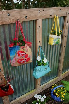 Another good fence idea! Made with corrugated metal and wood.  Brightly painted and decorated handbags repurposed into planters.