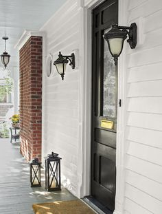 porch with view of exposed brick from relocated fireplace, light blue painted porch ceiling, lantern scones, black entry door, victorian whole house remodel Fireplace Wall, Living Room With Fireplace, Fireplace Surrounds, Door Storage, Tall Cabinet Storage, Black Entry Doors, Casement Windows, Built In Bookcase, Exposed Brick