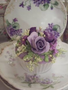 gorgeous bouquet cupcake : purple rose and green, on matching scalloped-edge saucer.