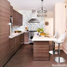 Caroline Beaupère designed a custom-made tile backsplash of delicate vines to bring a New York City kitchen to life. The Viking range is paired with a hood from Best Range Hoods. Andy Fleishman Maximus concrete floor tiles from Ann Sacks. Stools from ABC Carpet