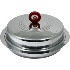 This wonderful, circa 1940s, art deco metal serving dish is accented with a single Bakelite red circle and orange dot handle. The fan designs around