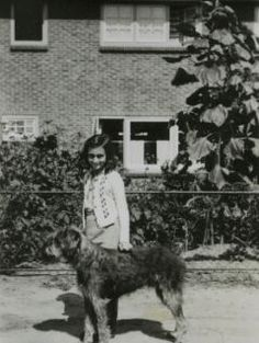Anne Frank with a dog in Laren, The Netherlands. The caption says: 'Anne with Isa's dog Dopy'.