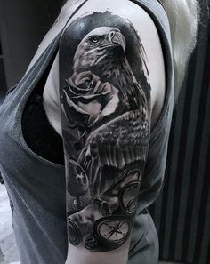 Black and gray sleeve tattoo. The tattoo consists of an eagle, a rose and a pocket watch that simply wants to make a statement with itself. It's definitely a head turner and has wonderful amount of detail out in it.