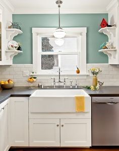 I love the white cabinets and clean subway tile next to the pretty aqua paint color (Benjamin Moore Kensington Green #710)