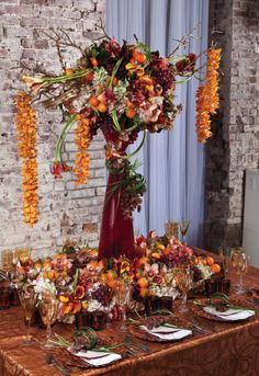 This  floral arrangement is a lush mix of fresh fruit and flowers,  including persimmons, oranges with the leaf attached (currently in season and available in supermarkets), magnolia leaves, red grapes, hydrangeas, different types of orchids including rust and chocolate cymbidium orchids, tiger vandas, and mango calalilies.
