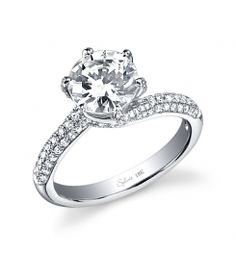 This unique 18K white gold diamond bridal engagement ring features a 1.00 carat round brilliant center diamond. Beautifully designed to accentuate the center diamond, this diamond engagement ring has a total of 0.57 carats of round diamonds flowing down the shank. The diamond engagement ring is available in any size or shape center, in 18K white gold or platinum. All Sylvie Collection diamond engagement rings are available with a flush fit matching wedding band. (For pricing on this diamond…