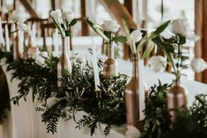 Grooms table decor with greenery, tulips and roses